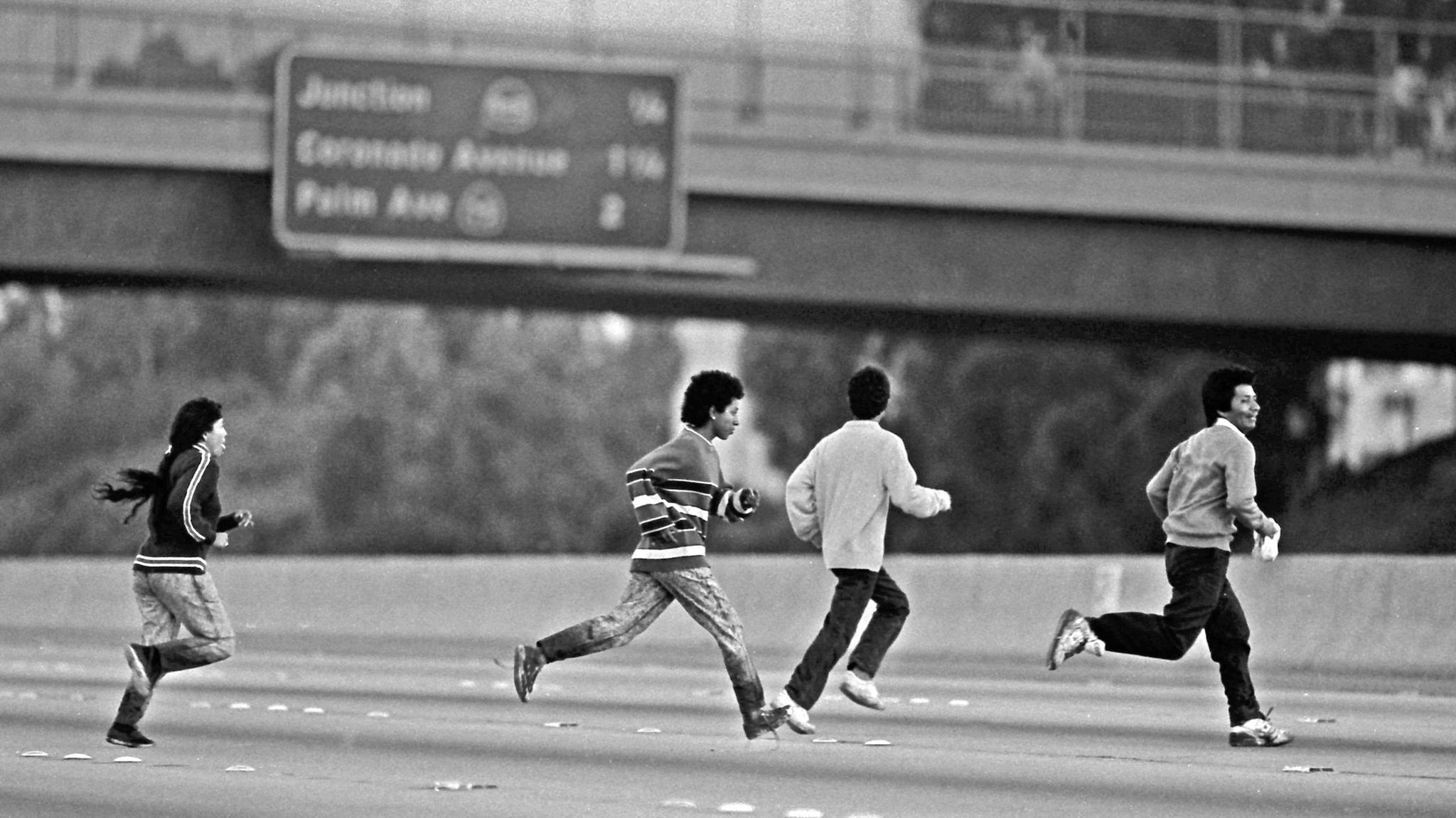 Young people sprint across the 5 Freeway with their pant legs still wet after walking in the nearby Tijuana River in this 1990 file photo.