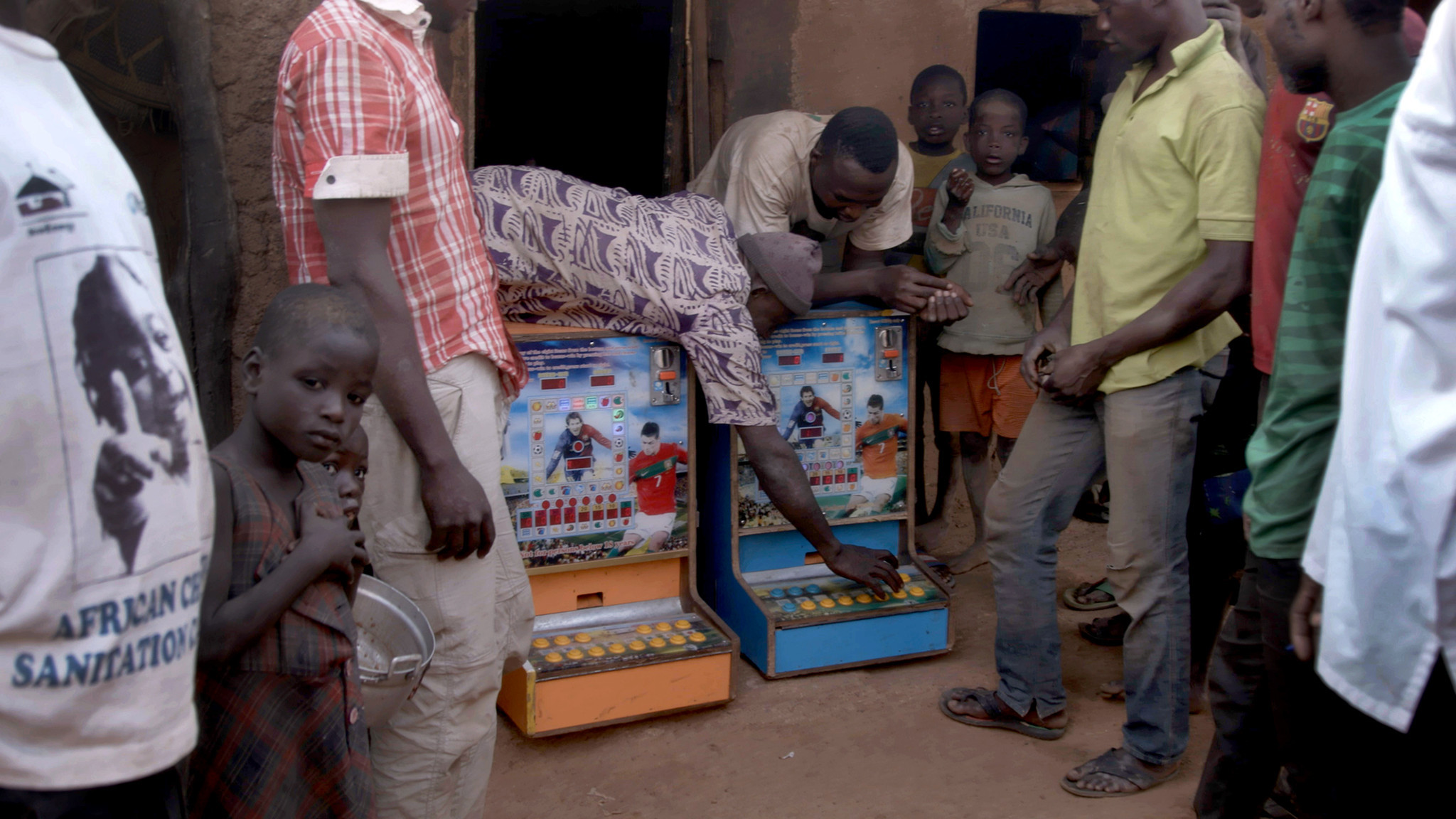Villagers bring two gambling machines out from a hut in Zamashegu, in Ghana's Northern Region.
