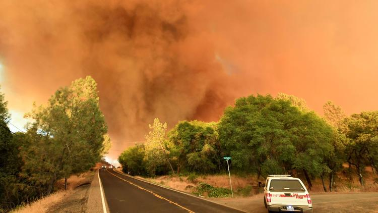 A plume of smoke rises as flames from the Wall fire approach Forbestown Road near Oroville, Calif., on July 8, 2017.