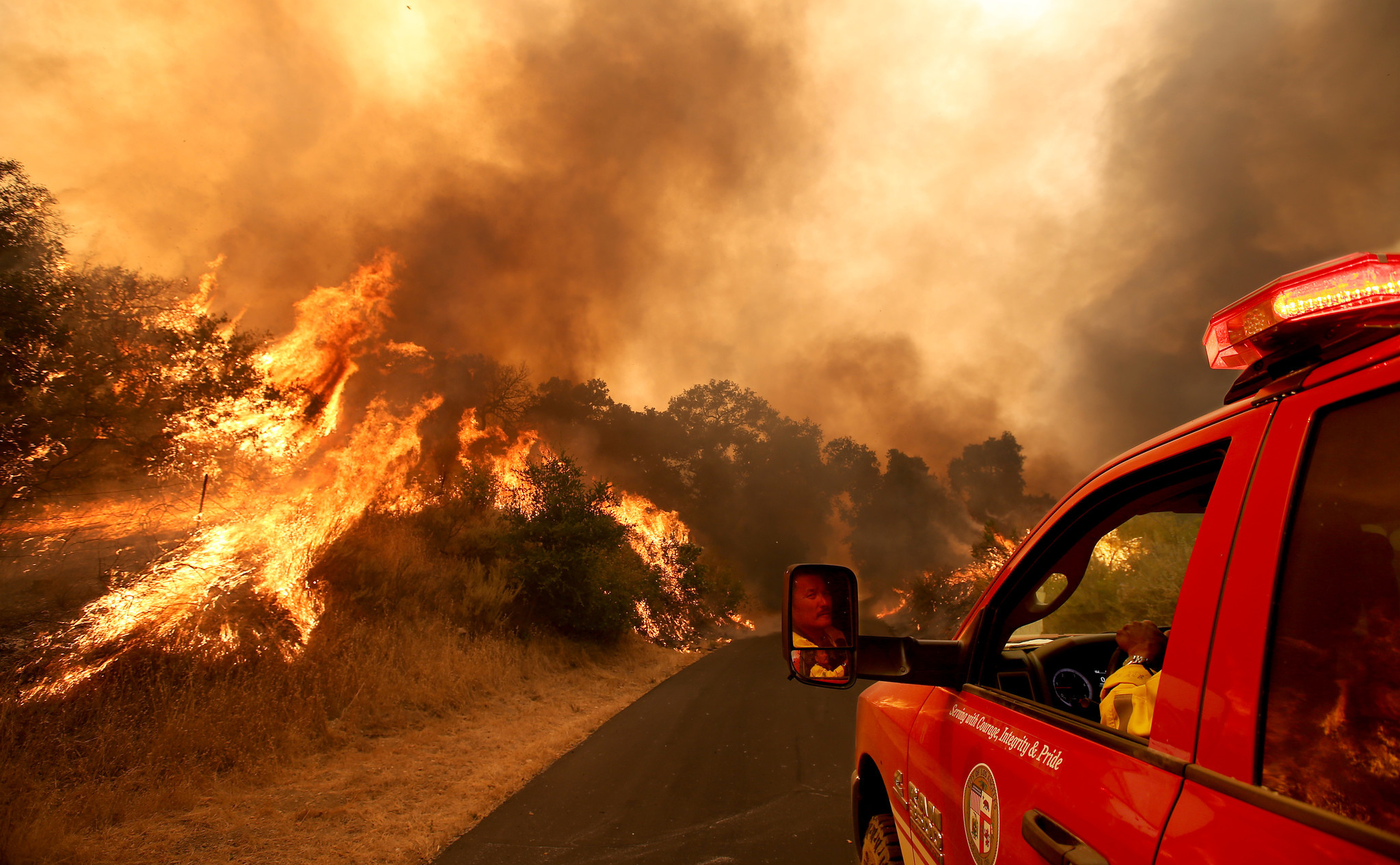 A firefighter maneuvers his vehicle down a private road as  the Alamo fire burns near Santa Maria on July 8, 2017. The fire has charred more than 6,000 acres in remote canyons along Highway 166, fed by dry brush and trees in an area that has not burned in many years.