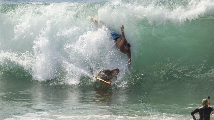 A bodysurfer and a bodyboarder catch the same wave Tuesday morning at the Wedge in Newport Beach.