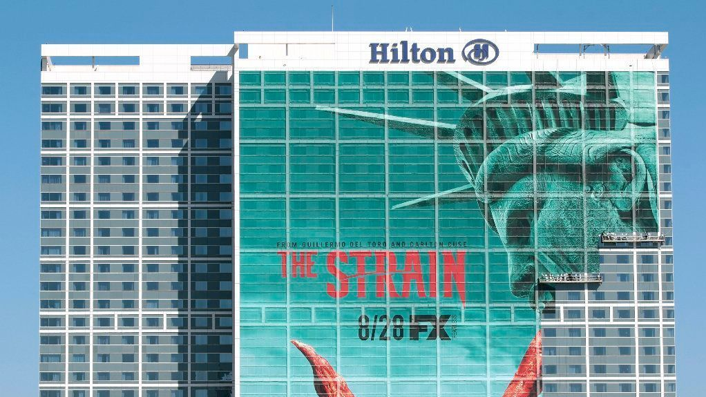 Workers on suspended scaffolding work on a giant mural on the front of the Hilton San Diego Bayfront hotel in preparation for Comic-Con 2016.