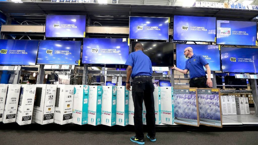 Employees adjust a television display at a Best Buy store in Cary, N.C.
