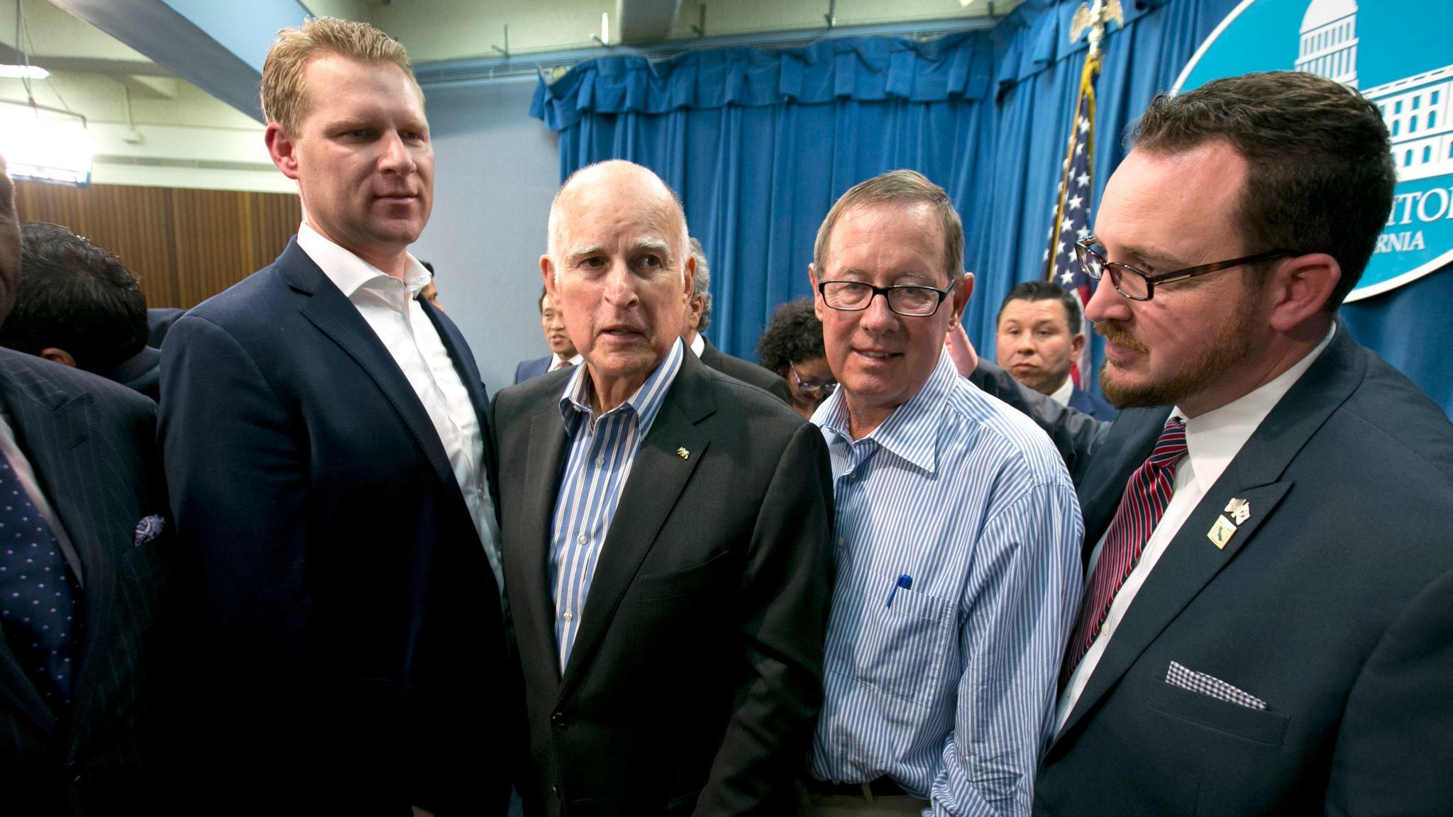 Gov. Jerry Brown, center left, flanked by Republicans who voted for the cap-and-trade extension: Assembly GOP leader Chad Mayes of Yucca Valley, Sen. Tom Berryhill of Modesto and Assemblyman Devon Mathis of Visalia.