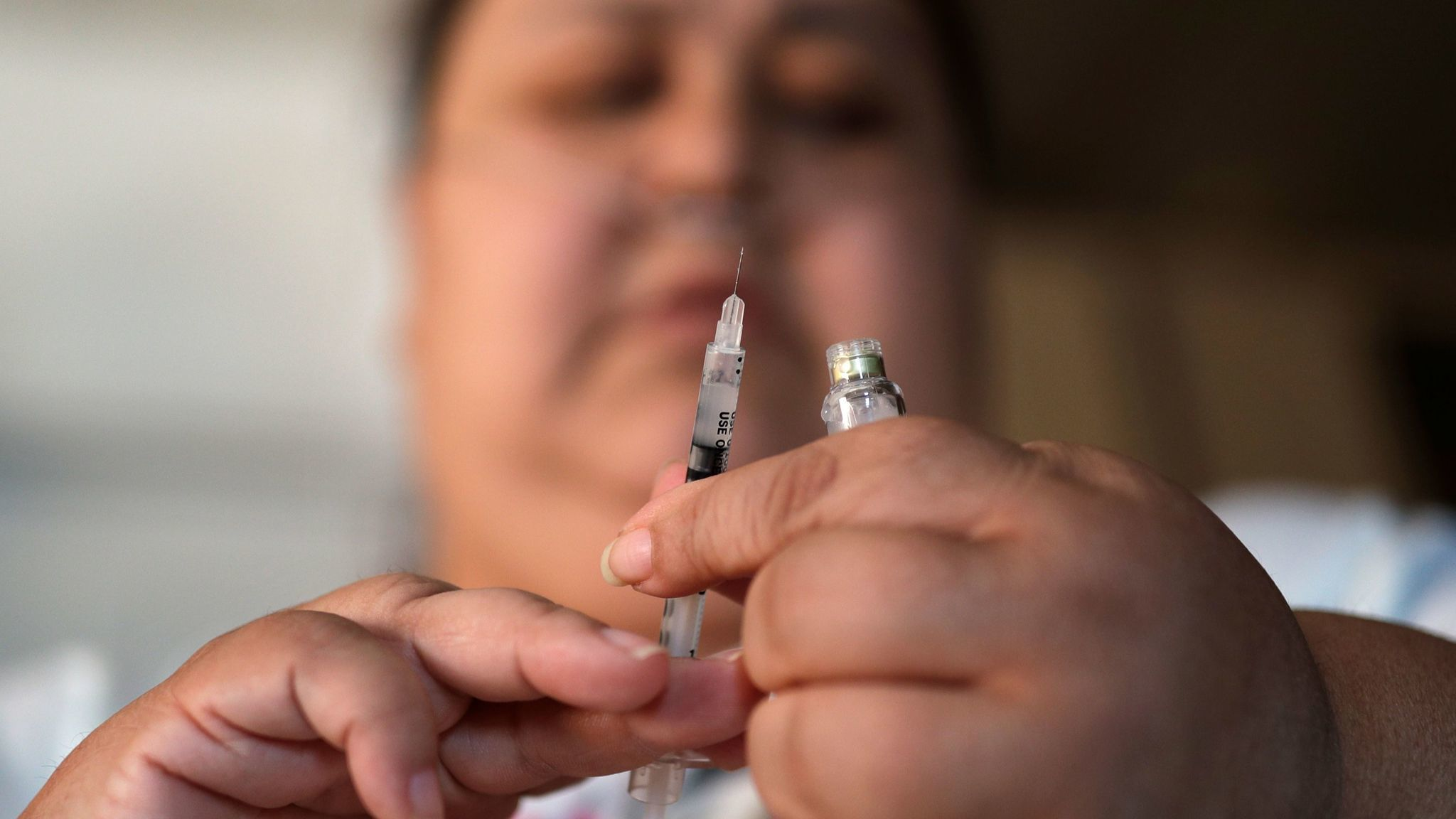 A woman with type 2 diabetes prepares to inject herself with insulin.