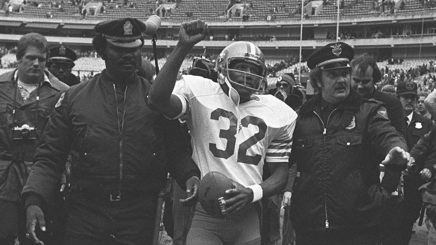 San Francisco 49ers running back O.J. Simpson is escorted from the field by police after the final NFL game of his career.