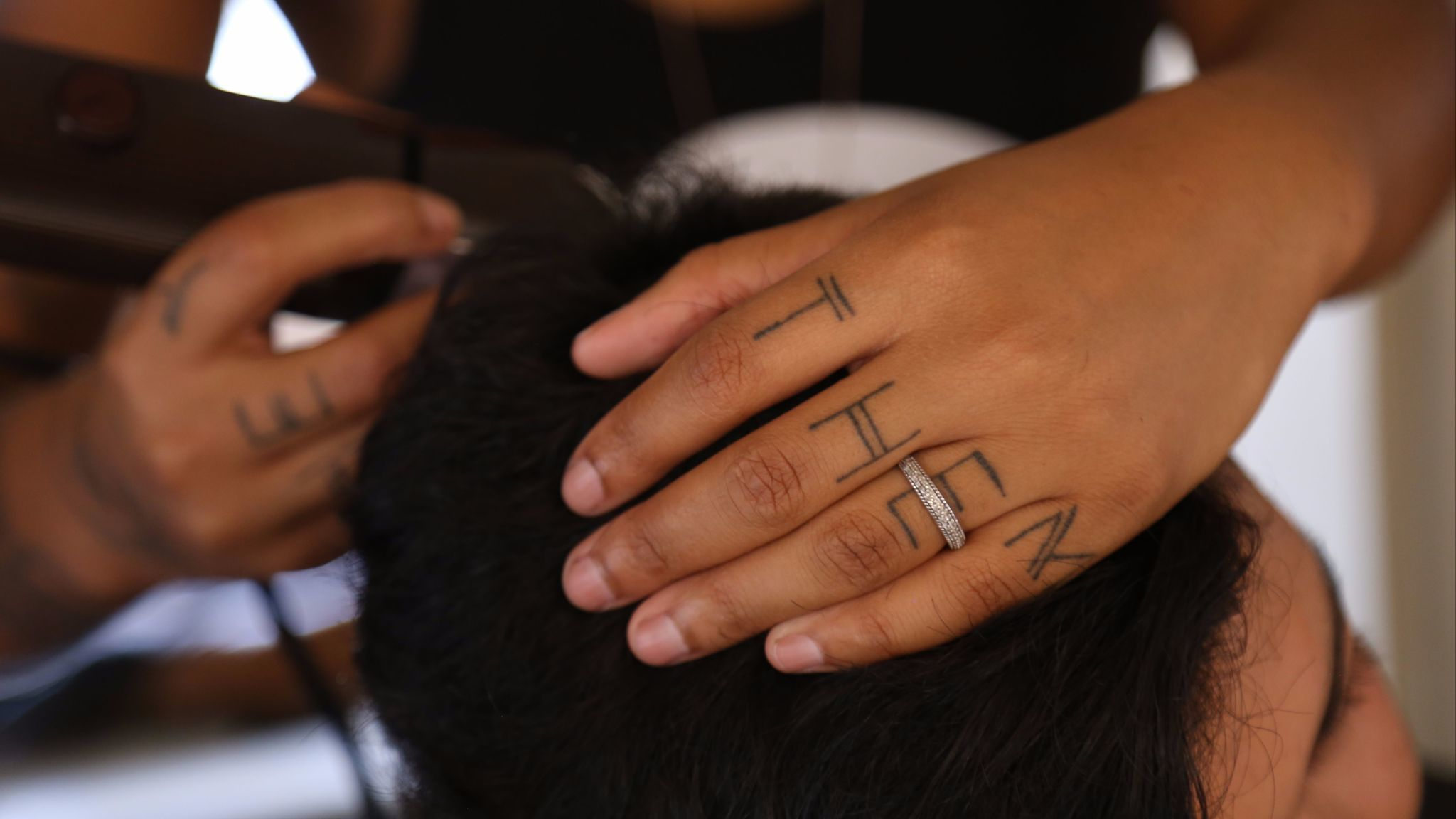 Madin Lopez, whose preferred gender pronouns 'THEY' and 'THEM' are tattooed on their hands, cuts hair in a trailer near the Los Angeles LGBTQ Youth Center in Hollywood.