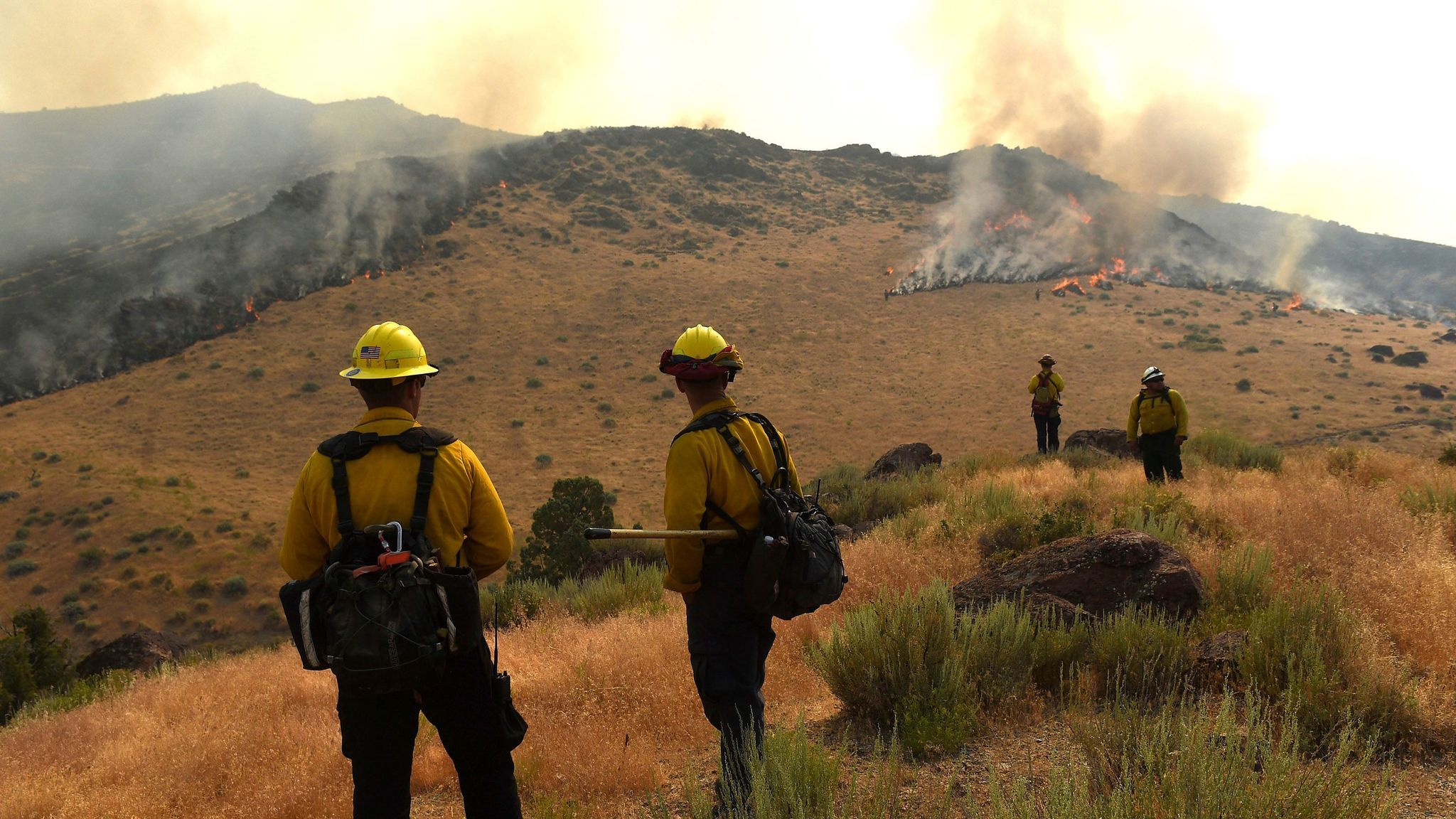 Crews work to protect a home site as they battle a wildfire along Pyramid Highway near Reno, Nev.