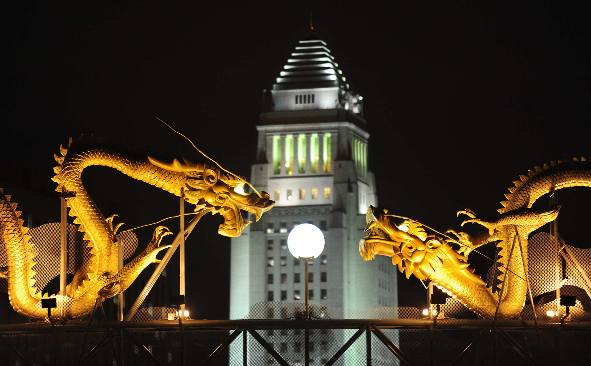 Los Angeles City Hall framed by dragon statues in Chinatown.