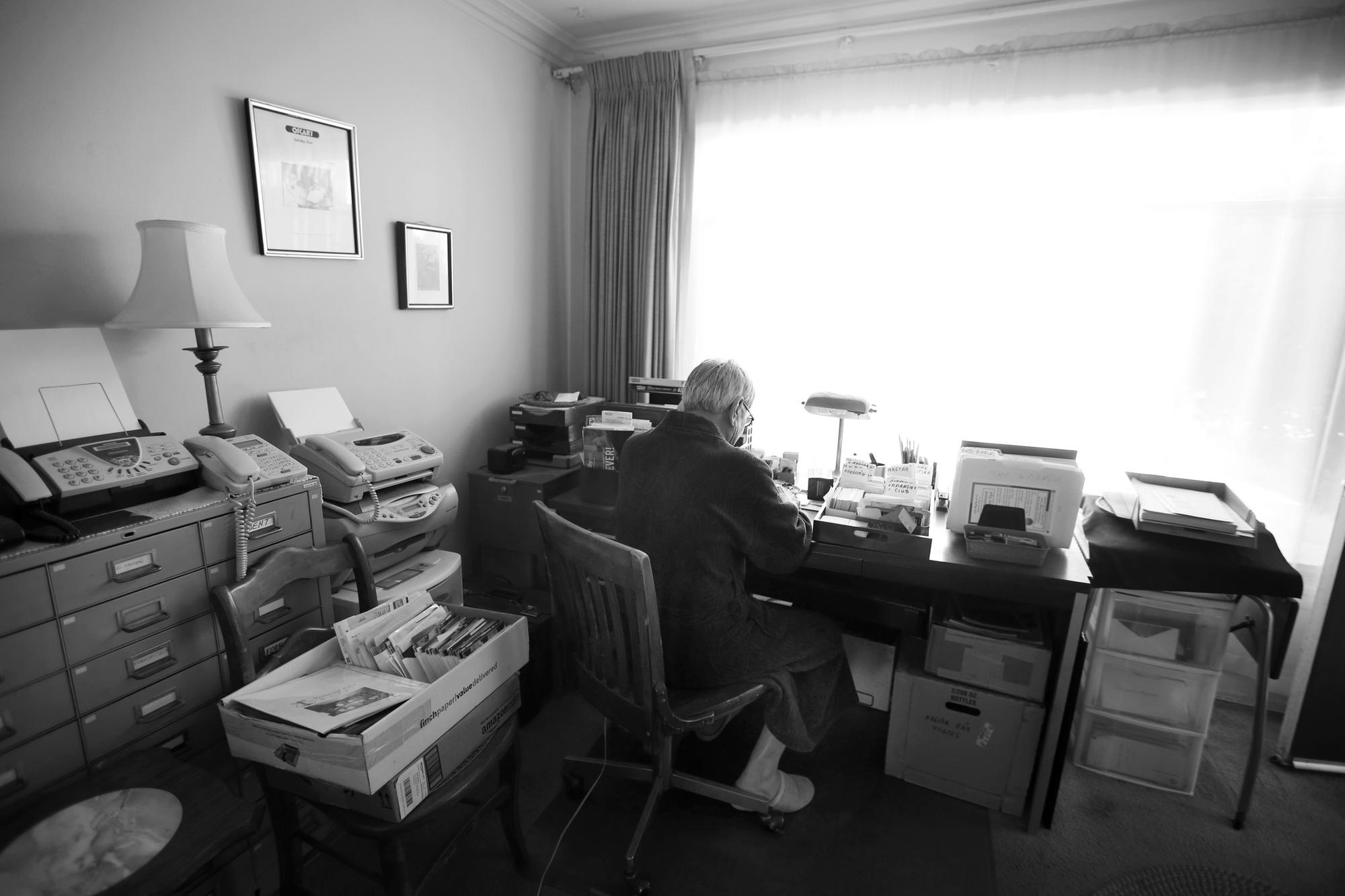 Steve Hideg, 85, looks though paperwork at his desk in his apartment in East Hollywood.