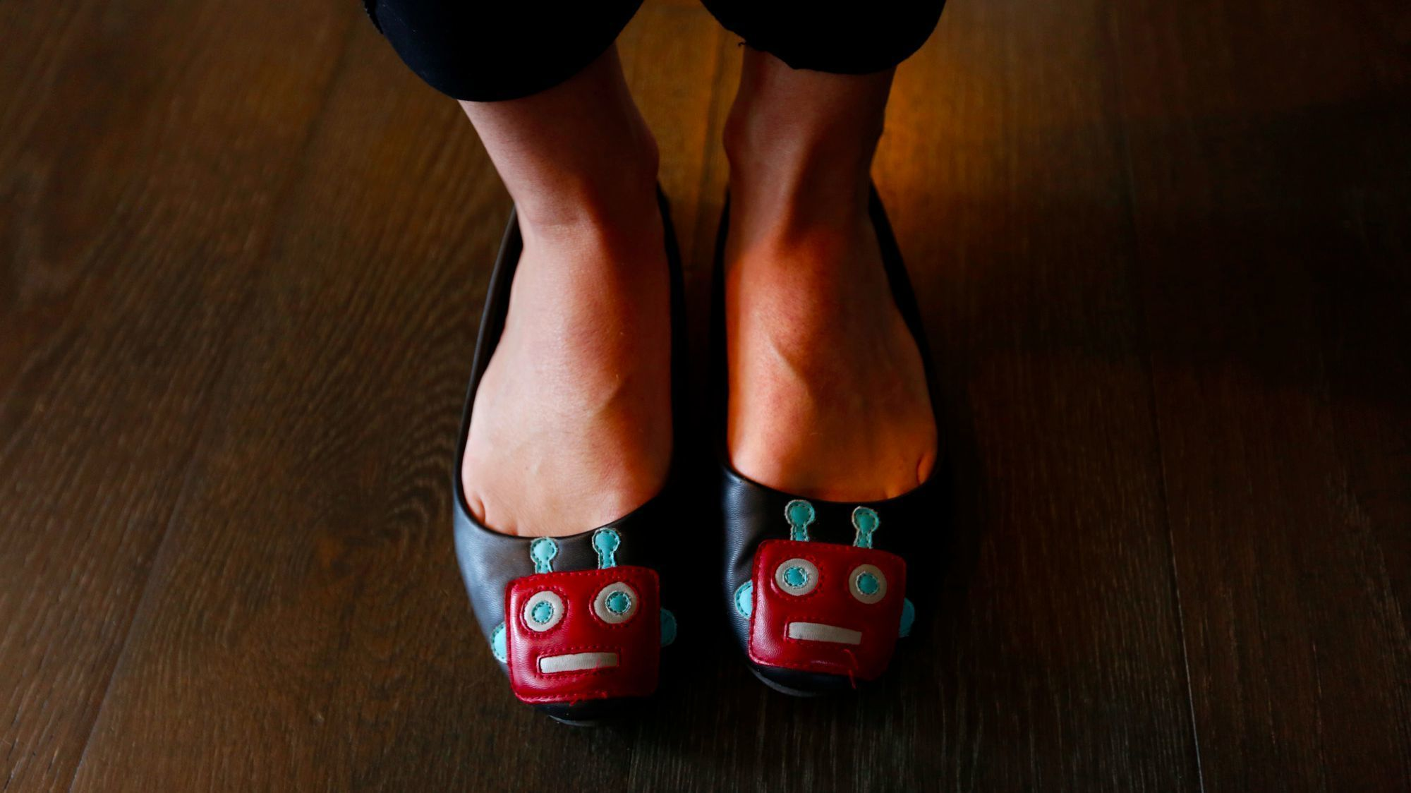 Alison Darcy, founder and chief executive of  Woebot, shows off her robot-themed shoes.