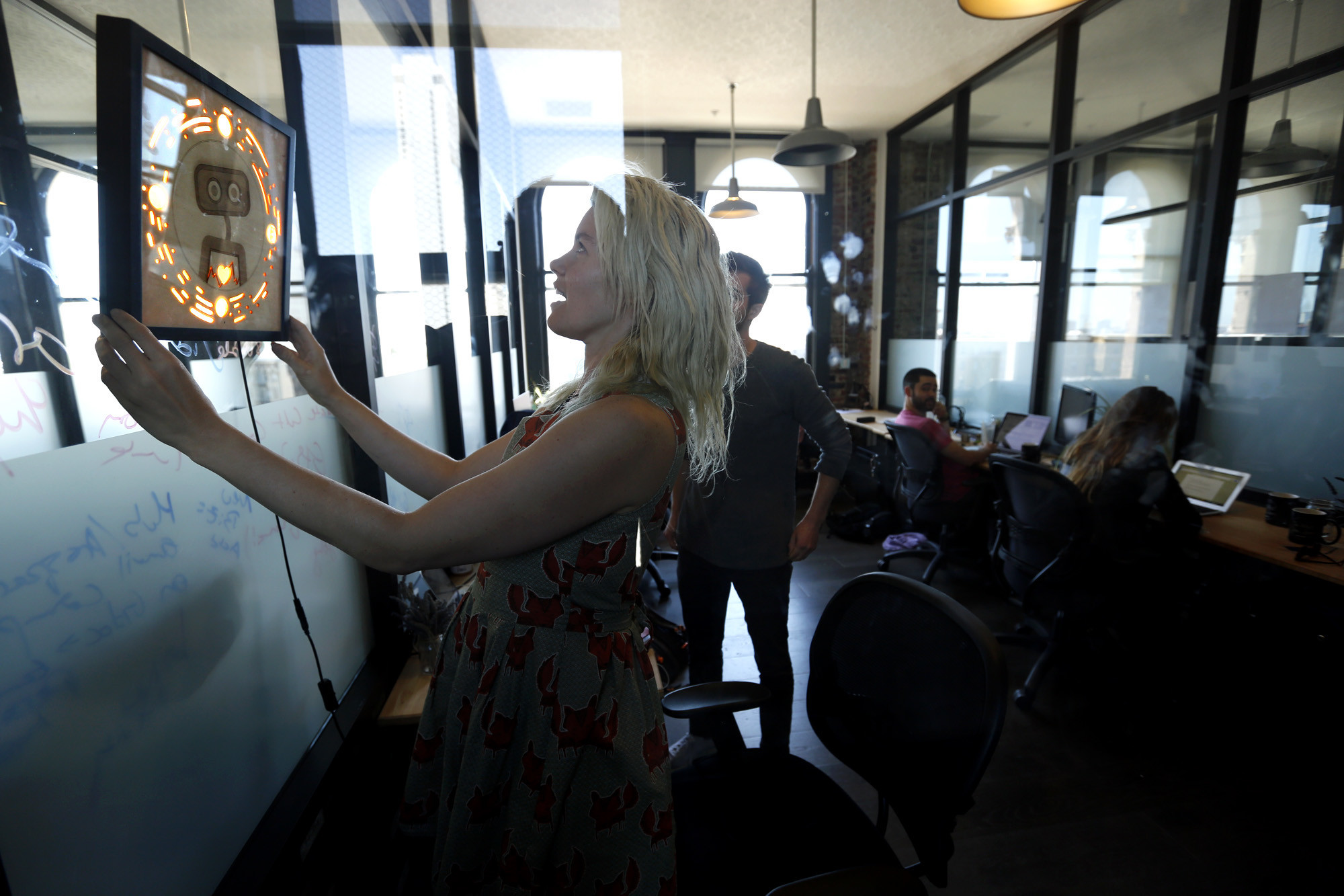 Pamela Fox, Woebot's chief technology officer, hangs a picture frame that contains the logo for the start-up as others work in their San Francisco office.