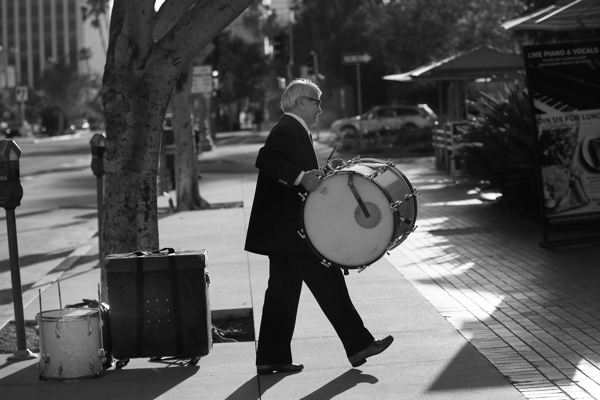 Wearing a suit and tie Steve Hideg, 85, carries his drums into Callender's Grill before his gig in L