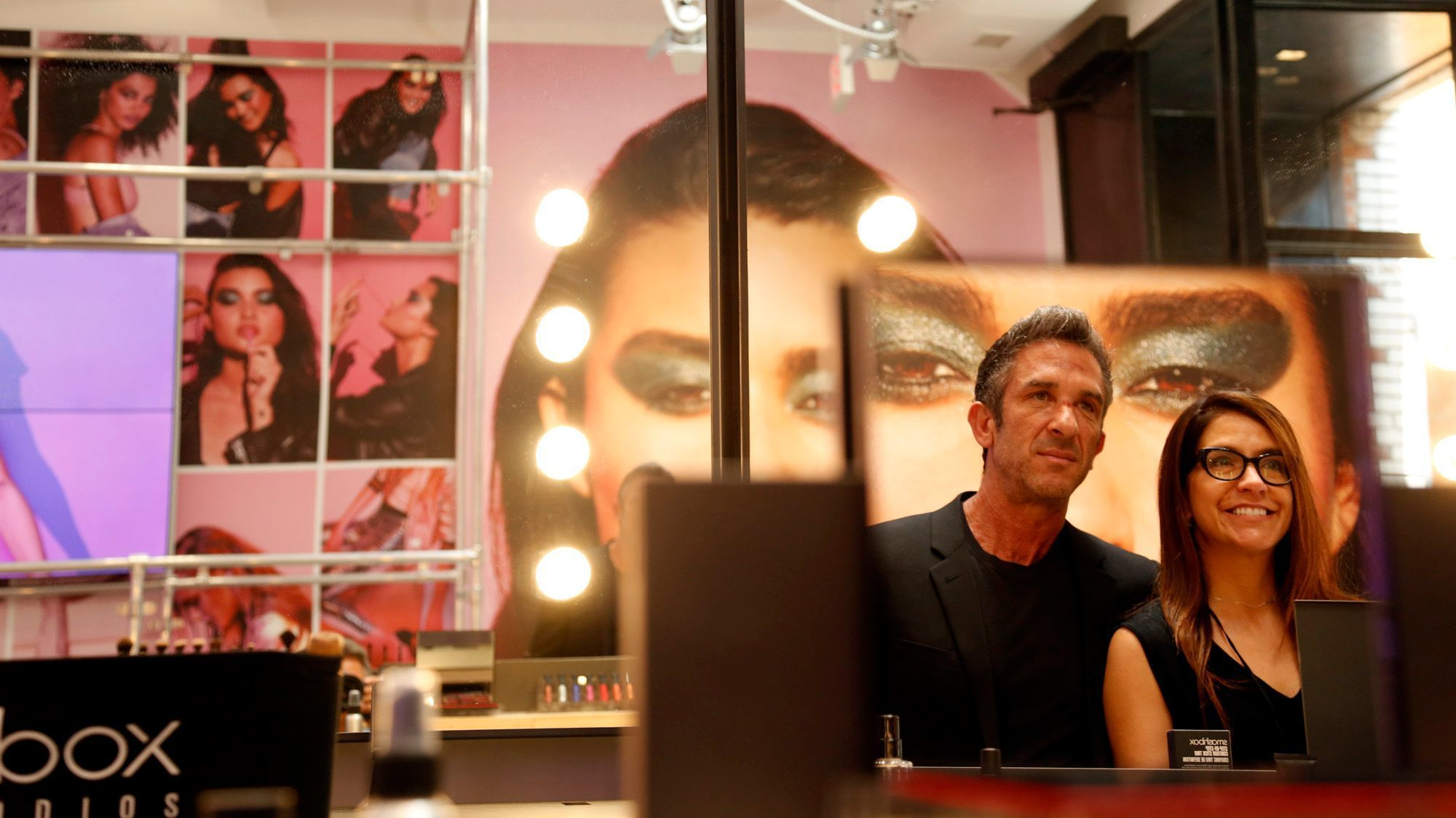 Reflected in a makeup mirror are photographer Davis Factor, Smashbox co-founder and senior vice president of global creative, and Beth DiNardo, global brand president of Smashbox, who stand inside their new Smashbox store on Abbott Kinney Boulevard in Venice.