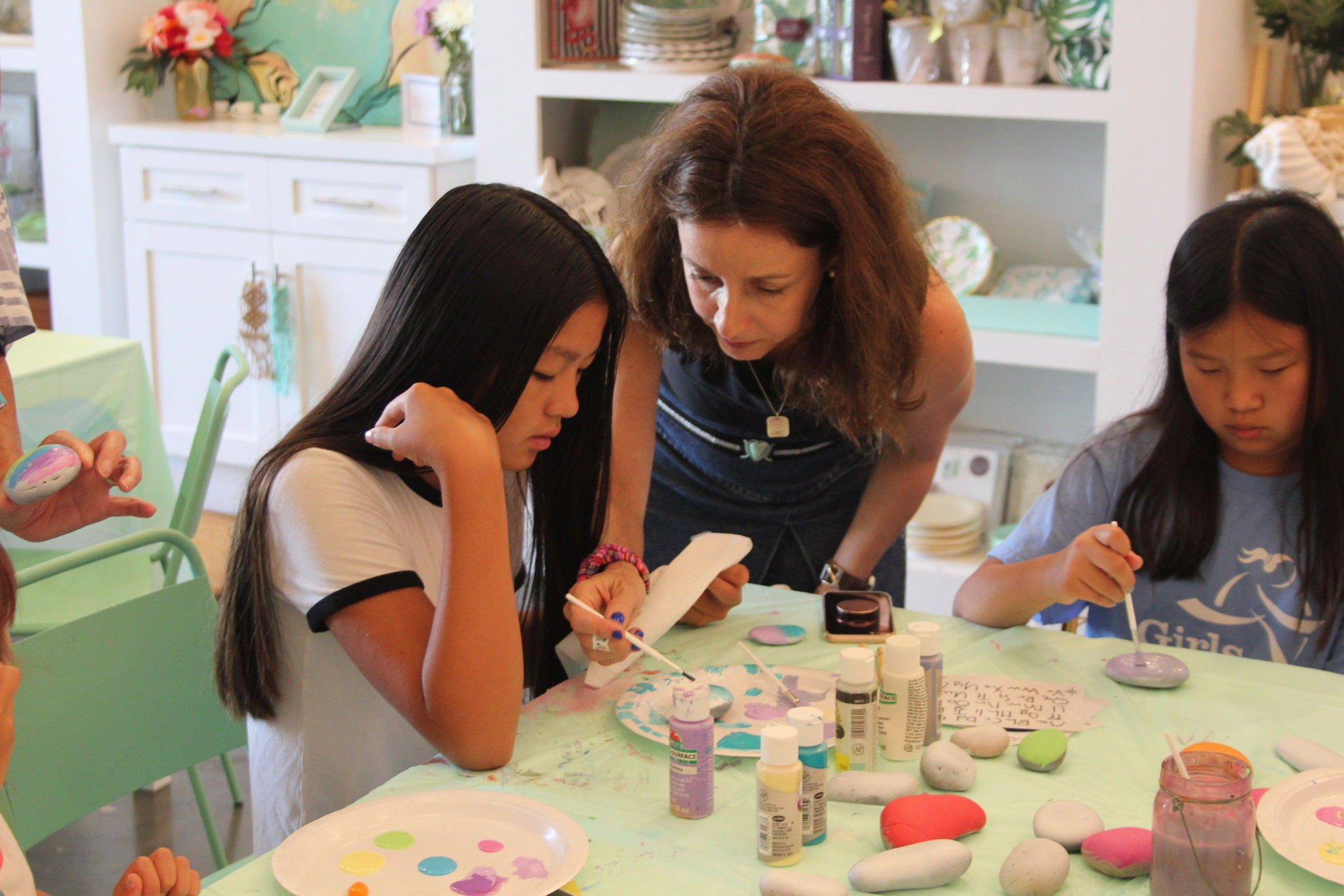 Carol Arêas helps a young artist paint her rock.
