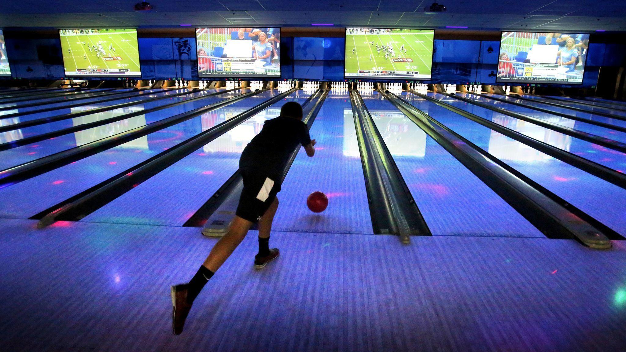A boy bowls in a bowling alley.