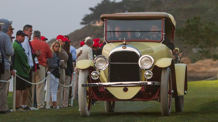Spectaors watch a 1917 Moon 6-45 Roadster drive onto the Pebble Beach lawn.
