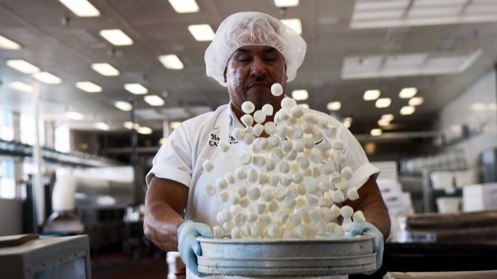 See's marshmallows, made in-house, get a good tossing from Arturo Barboza before heading off to other parts of the Los Angeles factory for further processing in 2013.