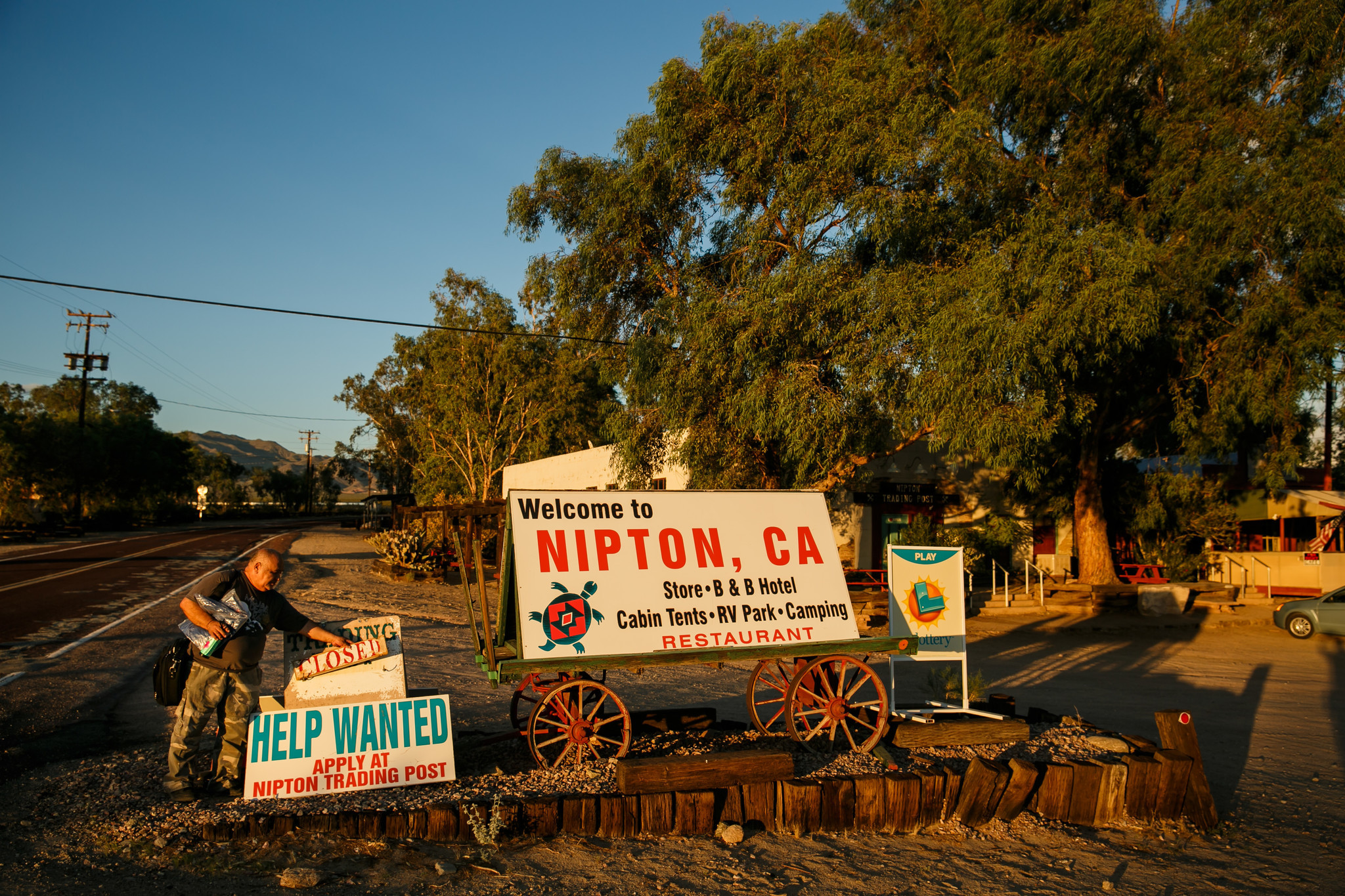 "Leo Hernandez changes the ""open"" sign to ""closed"" as the trading post closes for the day in Nipton."