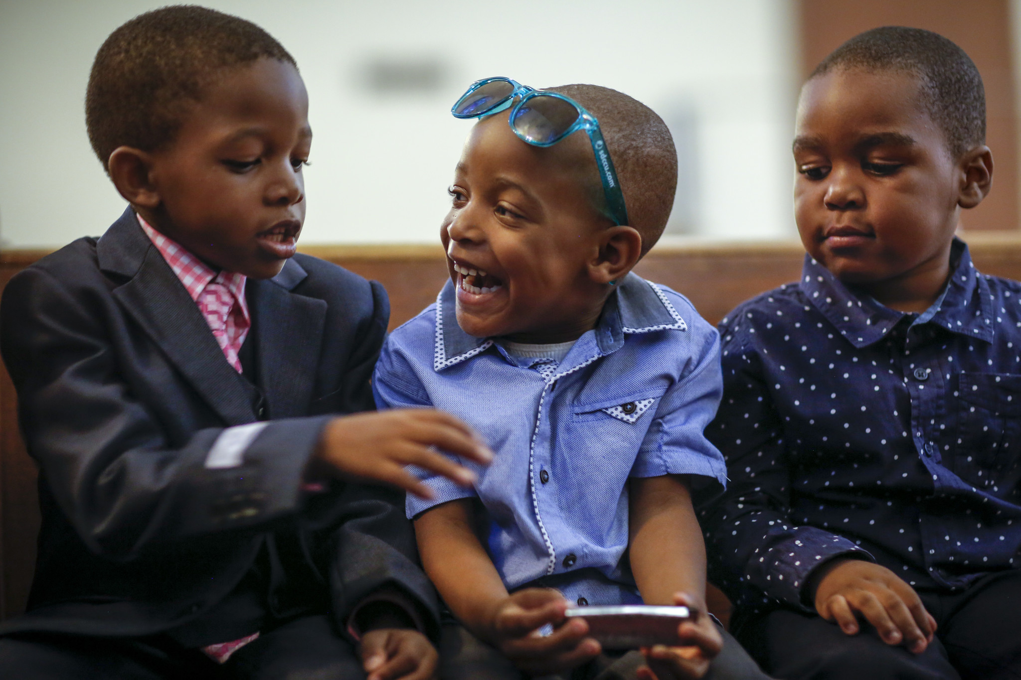 Ryan Labady, 5, Joshua Valsaint, 4, and Ruben Jacques, 4 from left, talk about playing the harmonica, in Joshua's hands, during a service at Christ United Methodist Church.