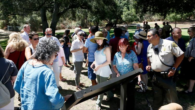 Attendees look at the new sign after the unveiling Friday in the western section of Crescenta Valley Park.