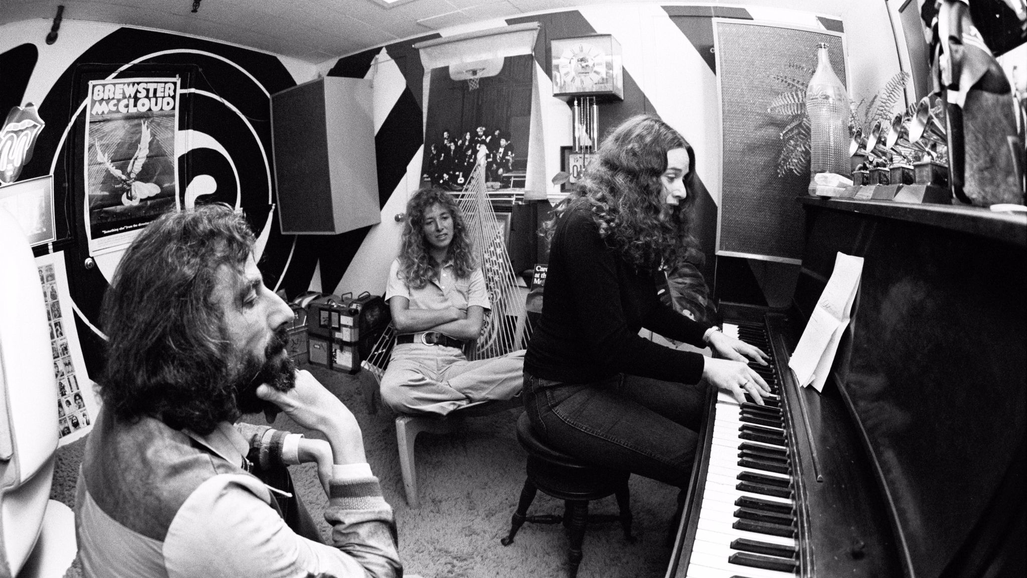 American singer-songwriter Carole King plays the piano to record producer Lou Adler, left, and her co-writer Toni Stern in Lou Adler's office in March 1971 in Los Angeles.