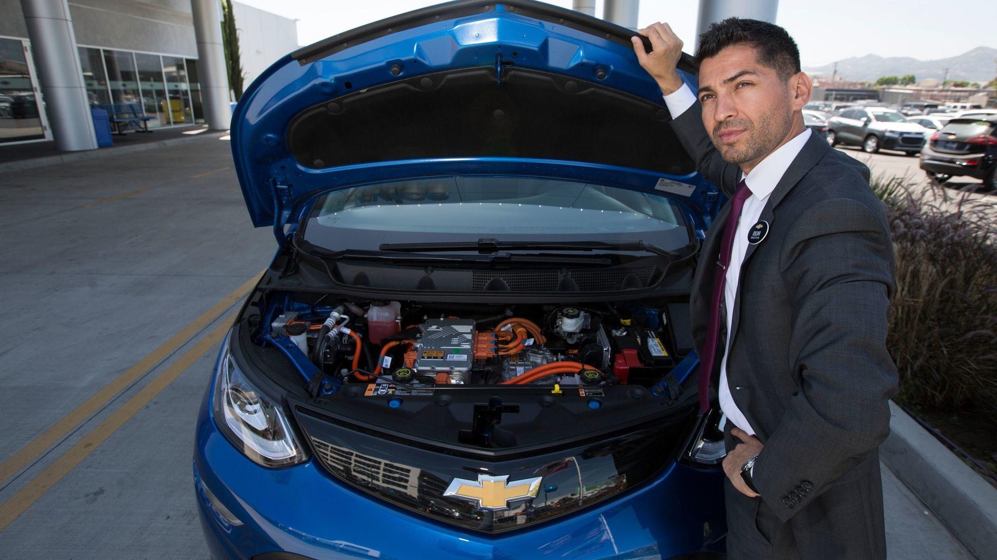 Oscar Gutierrez of Community Chevrolet in Burbank under the hood of a Bolt electric car.