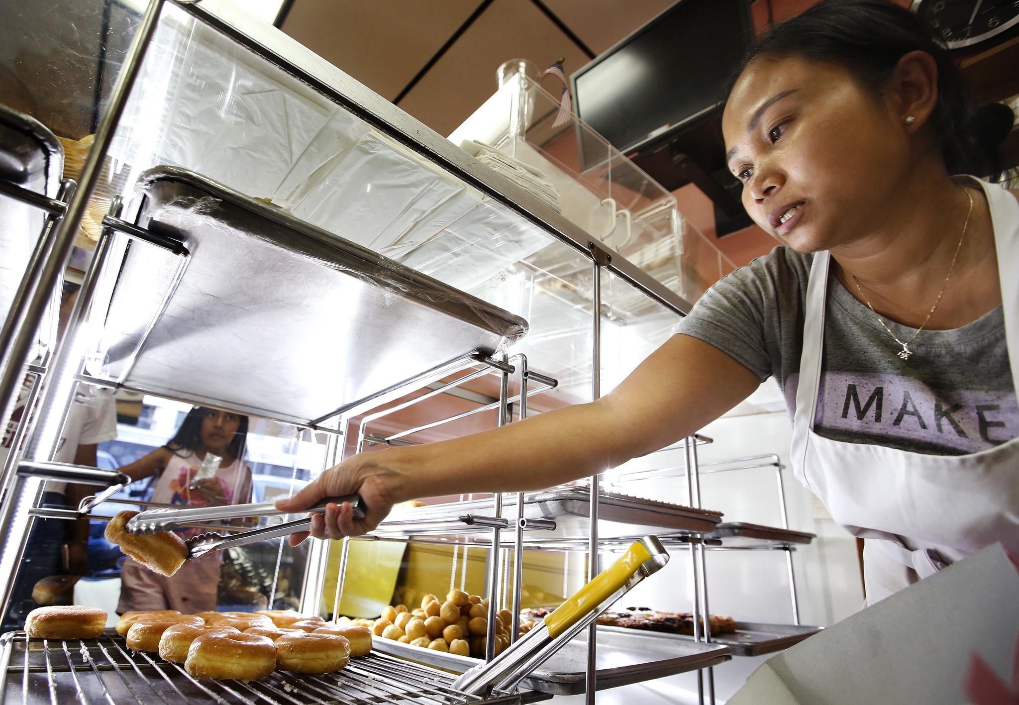 Srim Chhun, owner of Christina Donuts, fills a customer's order.
