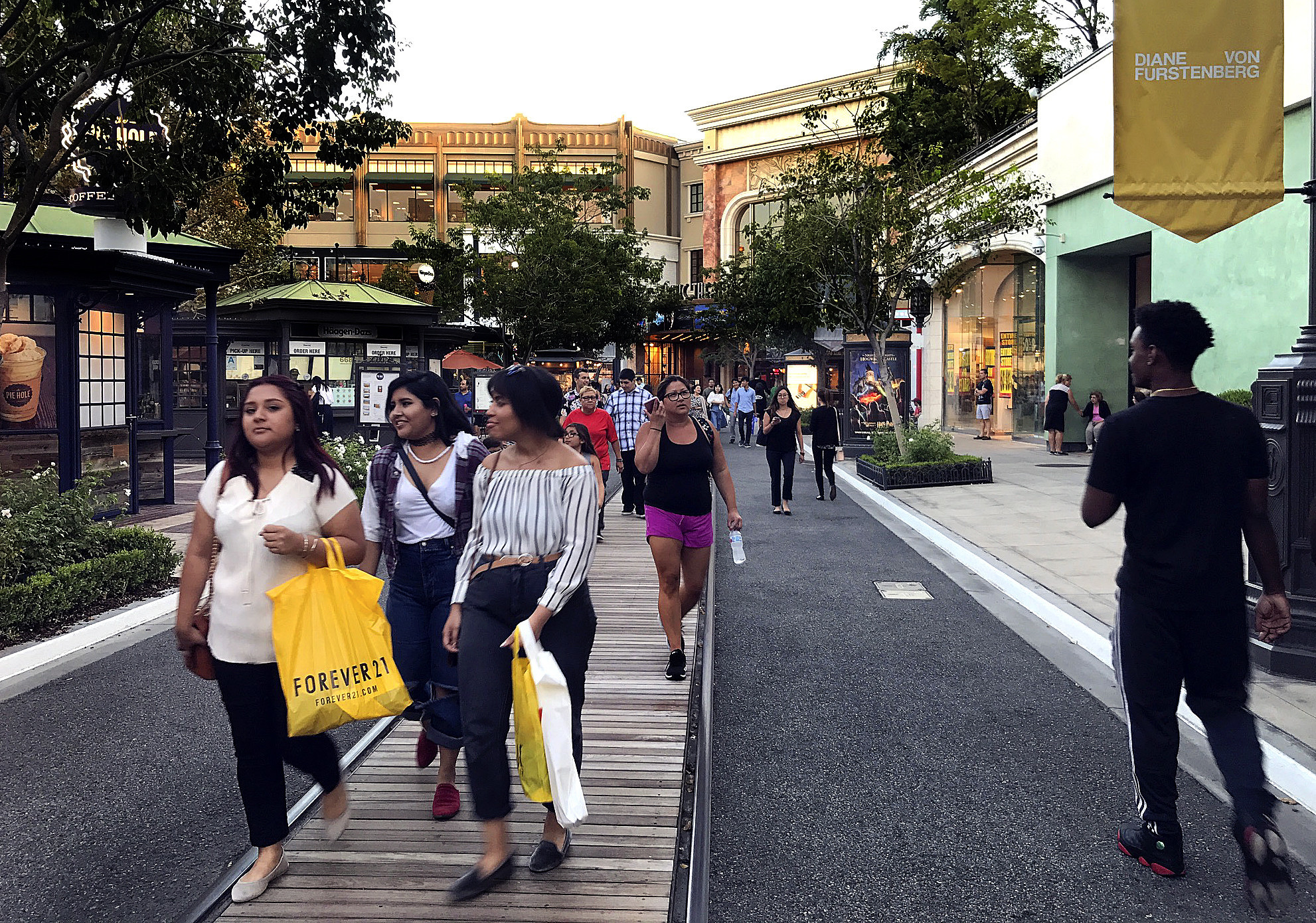 Shoppers stroll the grounds of the Americana at Brand shopping center in Glendale.
