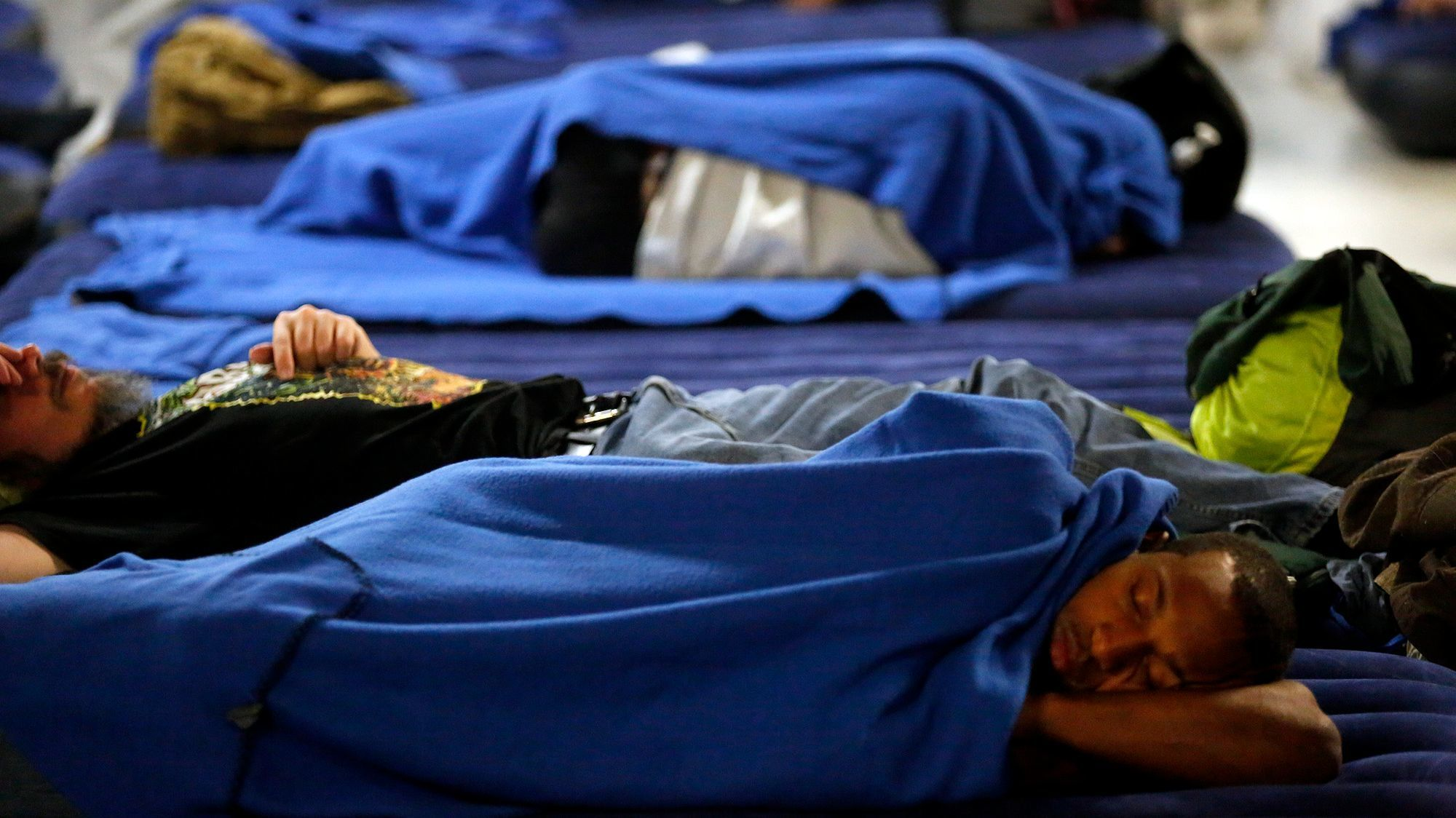 Men sleep on air mattresses in the overcrowded Union Rescue Mission.