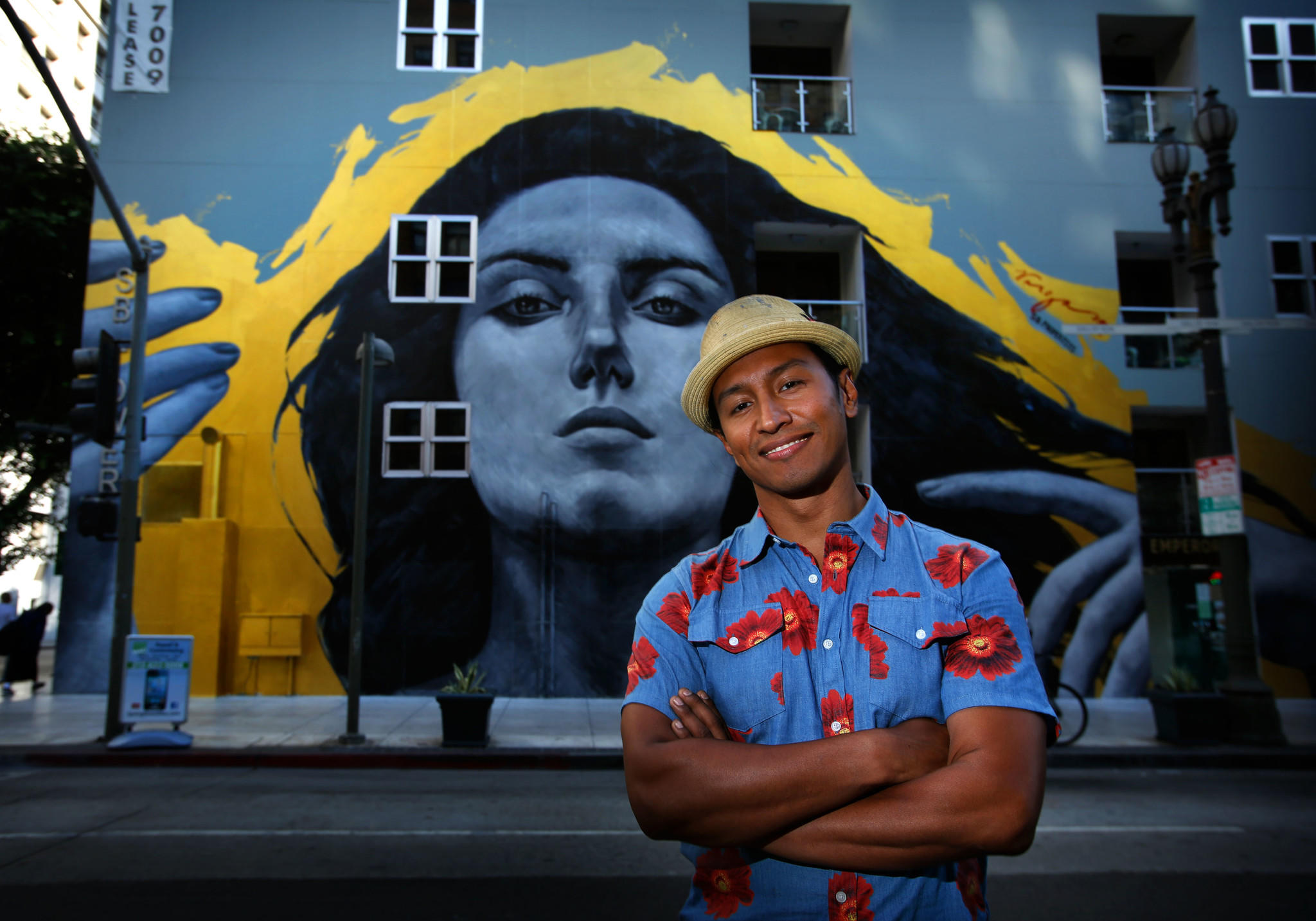 """Robert Vargas poses in front of his """"Our Lady of DTLA"""" wall mural at 6th and Spring streets in 2013."""
