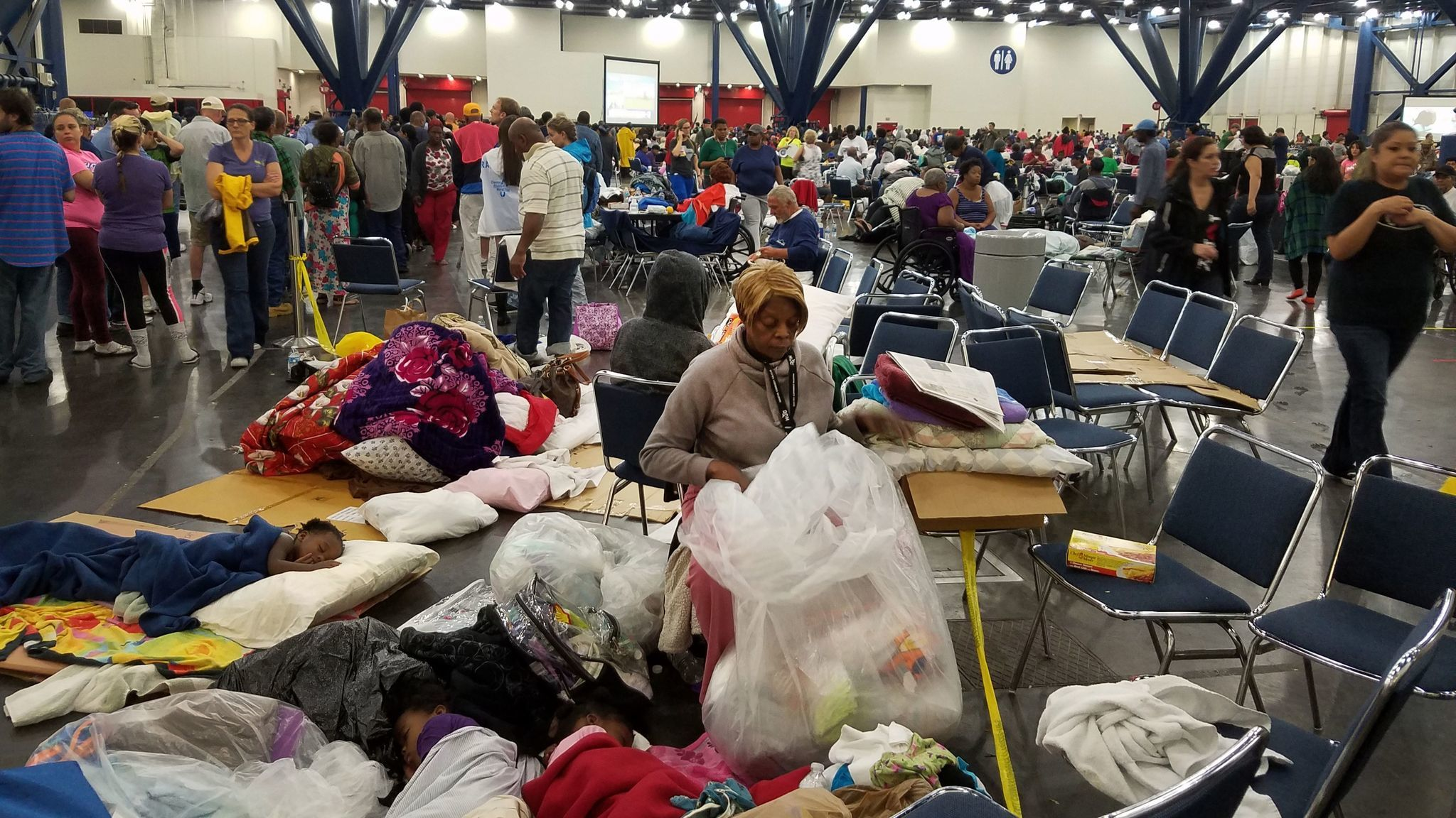 A woman sorts through clothing donated for those who have taken shelter at the George R. Brown Convention Center in Houston because of Hurricane Harvey.