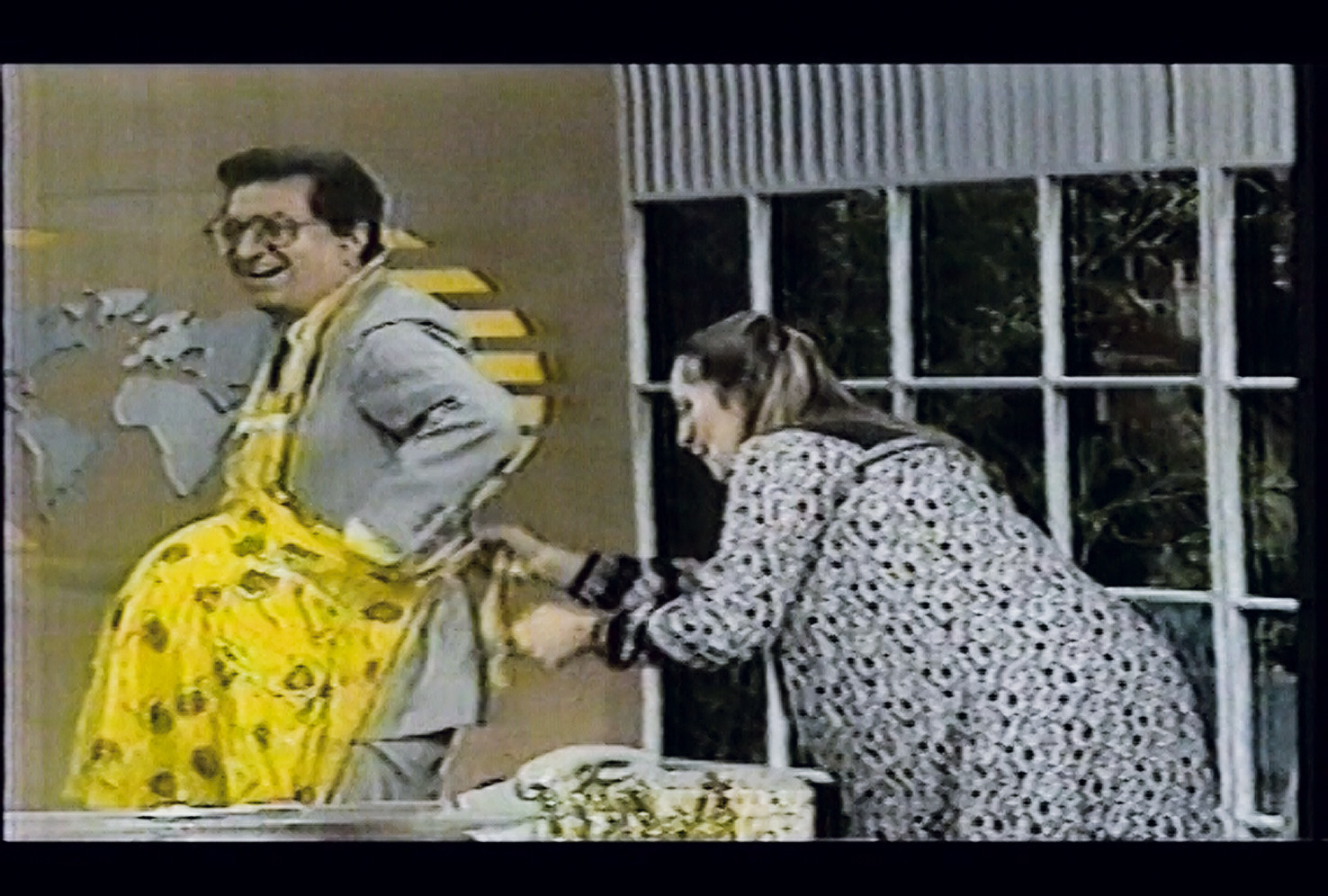 "Maris Bustamante puts an apron on television talk show host Guillermo Ochoa as part of the performance ""Madre por un día"""