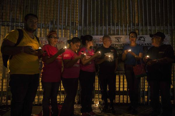 Activists pray for the continuation of DACA during a protest at the border wall in Tijuana on Monday. (Guillermo Arias / AFP/Getty Images)