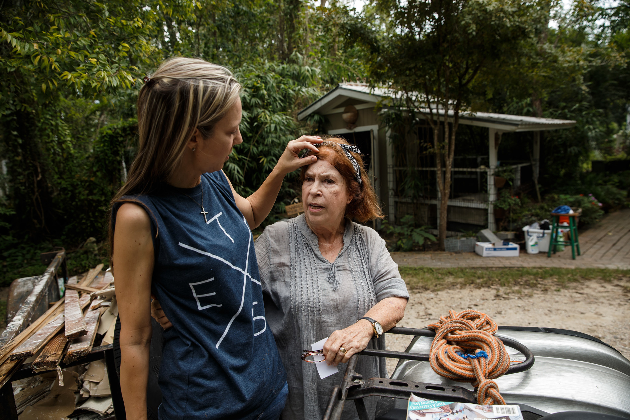 Jenny Sanders fixes Sue Bown's hair as they watch Sue's car get towed away after it was damaged by floodwaters.