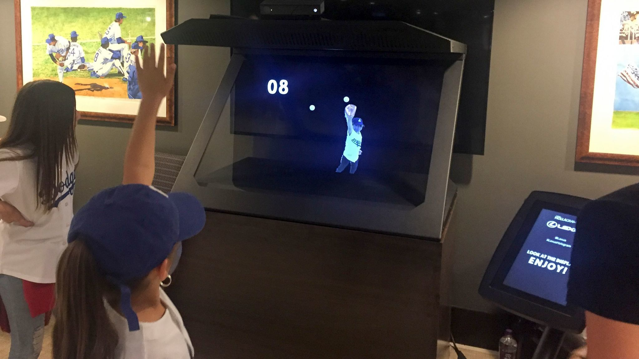 A girl at Dodger Stadium watches her hologram catch baseballs in a virtual glove.