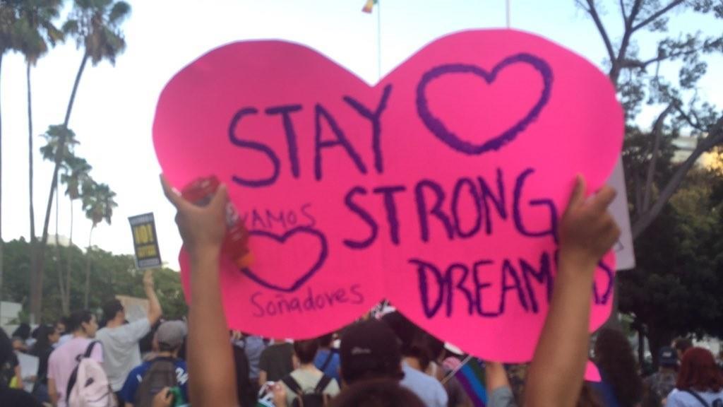 Zuleyma Chazari, a DACA recipient and USC student, hoists a sign outside City Hall. (Sonali Kohli / Los Angeles Times)