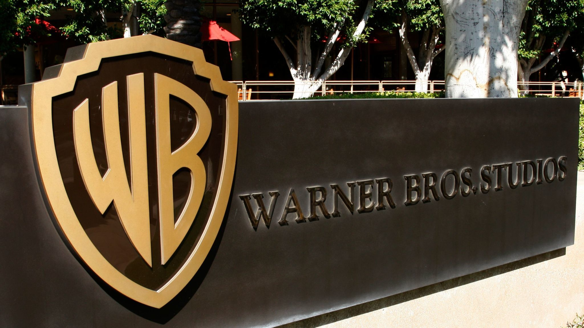 The Warner Bros. logo is prominent outside the studio lot in Burbank.