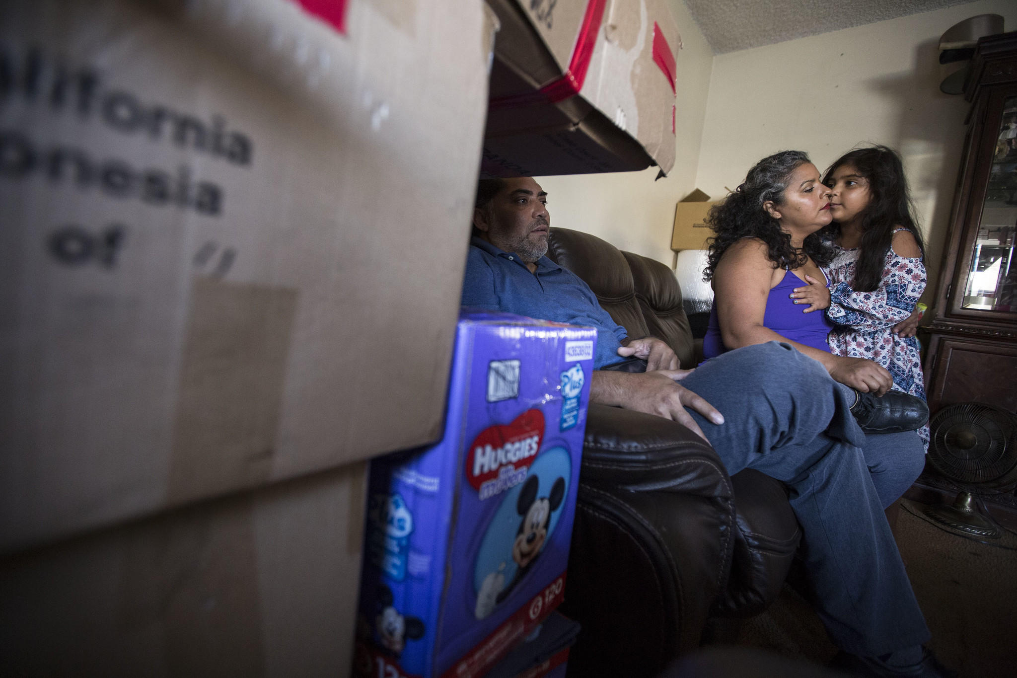 Ricardo Madrigal and his wife, Maria Barrancas, and their daughter Luz, 6, relax in their apartment after packing up their belongings.