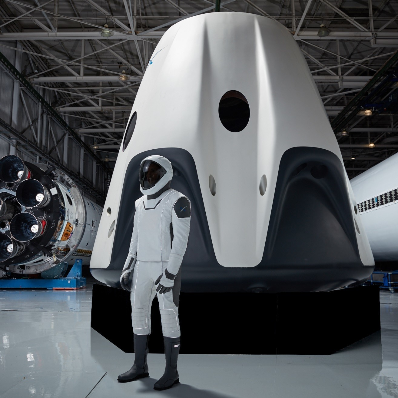 A person wears the SpaceX astronaut spacesuit and stands near the Dragon 2 capsule.