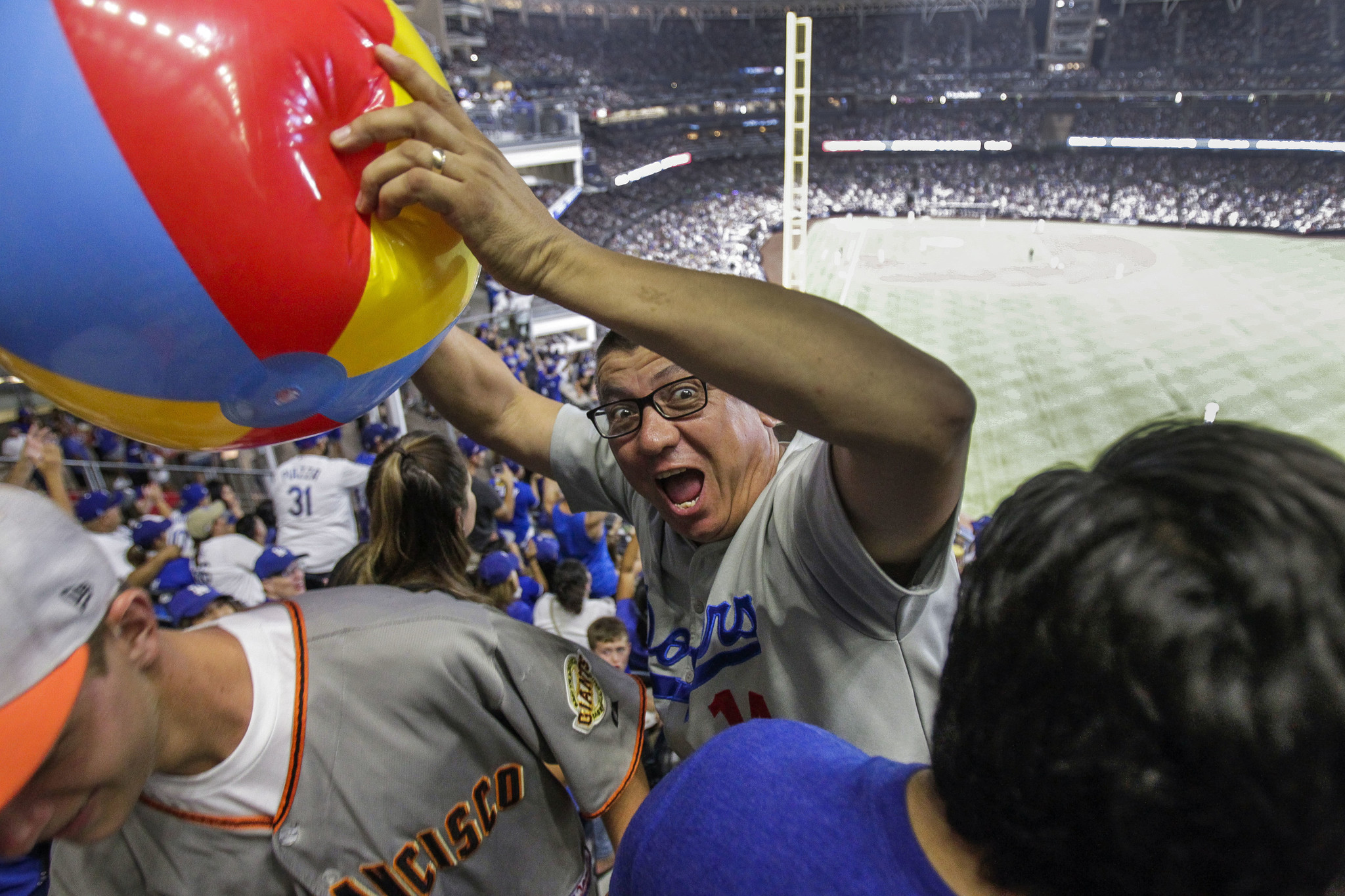 A Pantone 294 Dodgers fan club member grabs a beach ball as he and fellow Pantone 294 fans take up a section of seating during the Dodgers vs. San Diego Padres game at Petco Park.