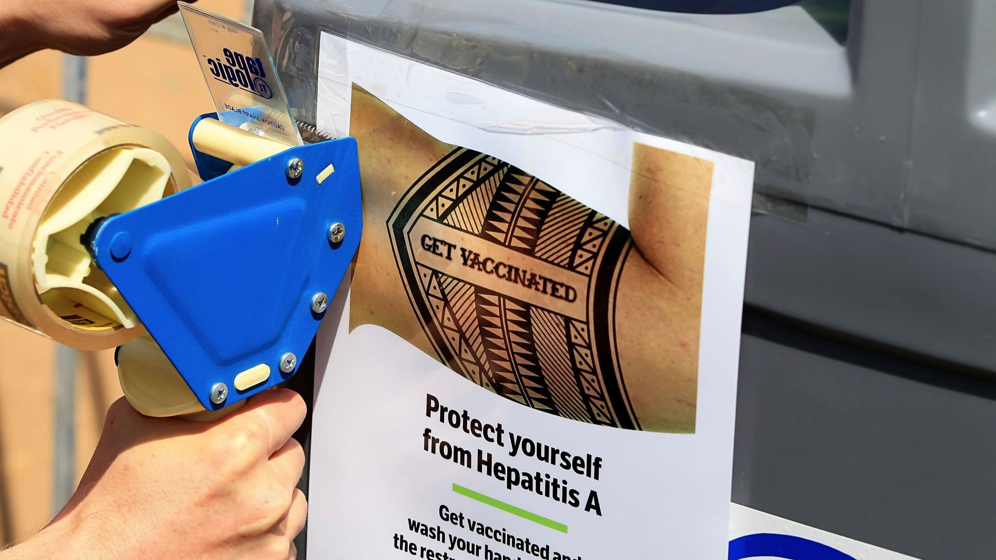 A worker tapes signage telling people to get vaccinated to protect themselves against Hepatitis A in downtown San Diego.