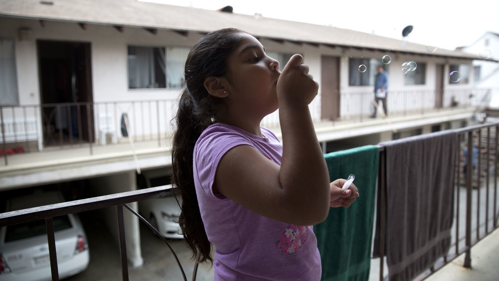 As her family packs the car to move, Luz Madrigal, 6, blows bubbles on the balcony of her apartment in Gardena.
