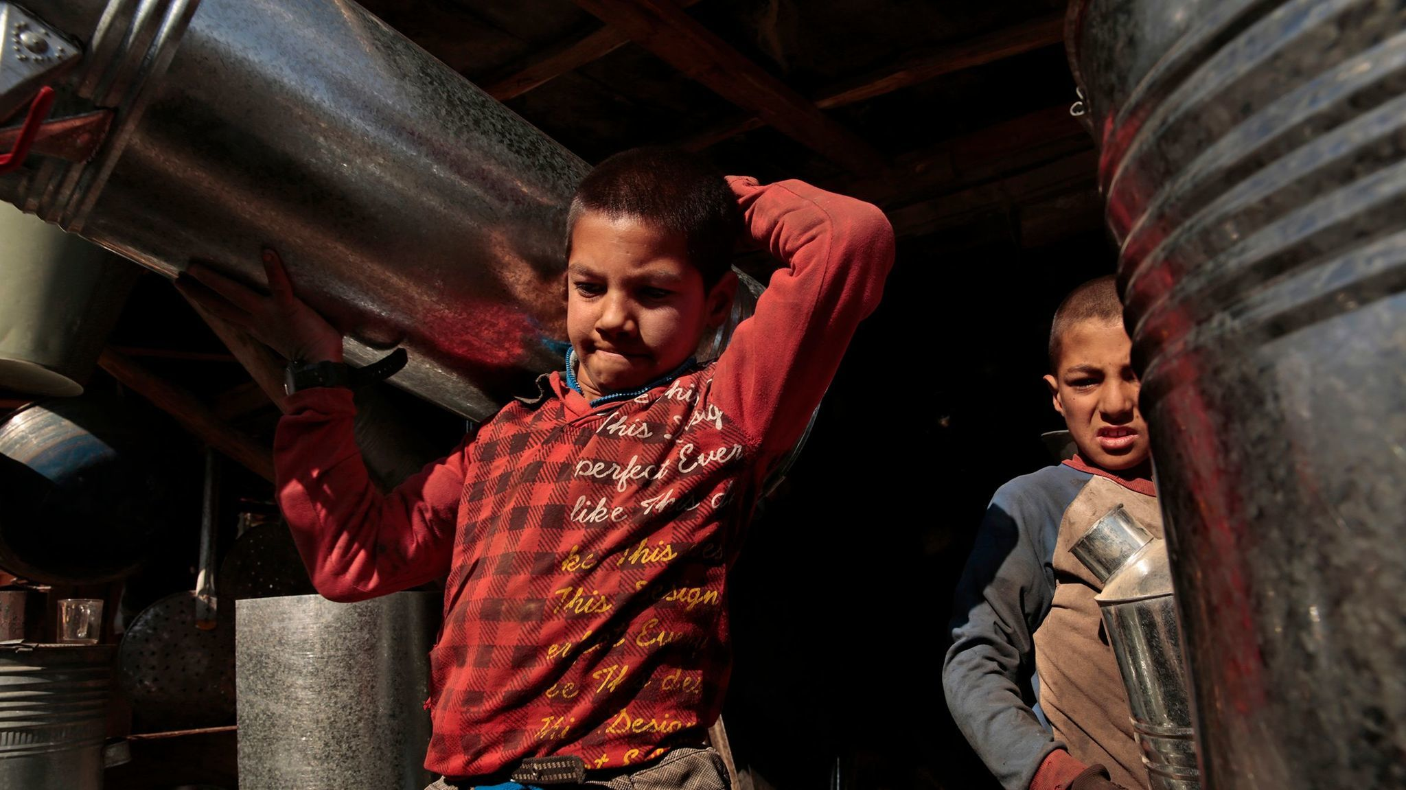 Brothers Hekmat, 12, left, and Qudratulla, 9, as they work in a metal shop in Kabul, Afghanistan, where they help make water heaters and other metal items for $6 per week, in 2014