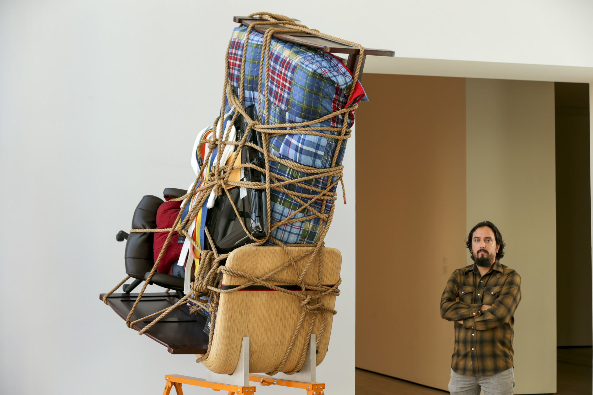 Artist Camilo Ontiveros with a sculpture he created with the belongings of a DACA recipient.
