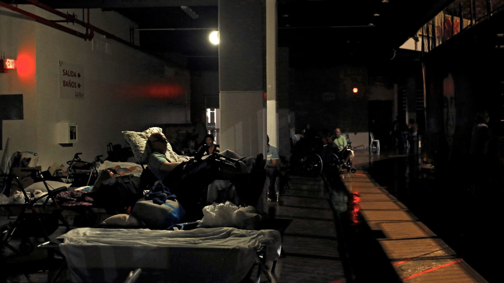 Evacuees rest in almost complete darkness in Roberto Clemente Coliseum, a major  shelter in San Juan.