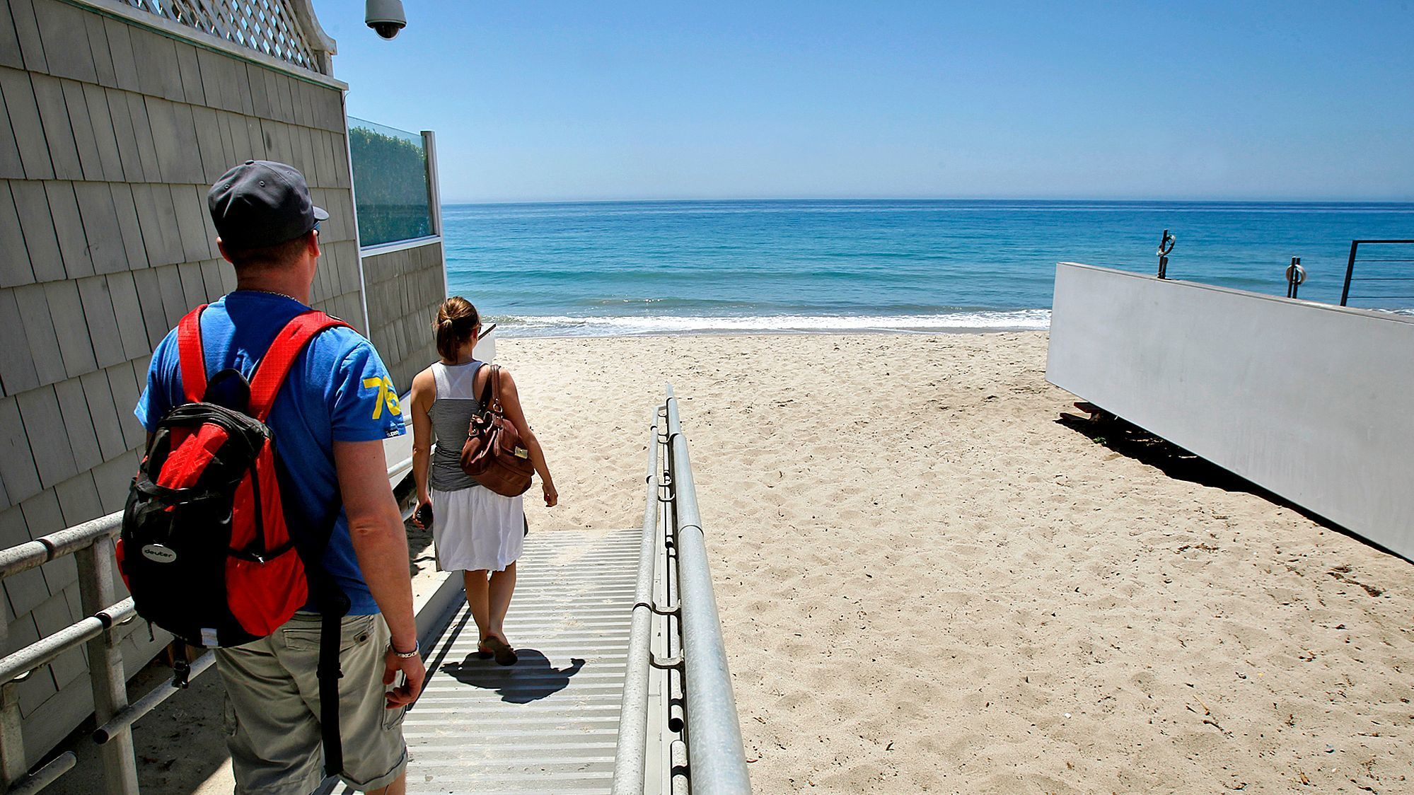 Beachgoers get to Carbon Beach in Malibu through a public accessway alongside David Geffen's former home.