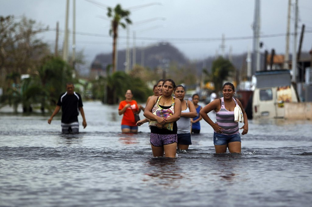 People walk on a flooded street in the aftermath of Hurricane Maria in San Juan, Puerto Rico on September 22, 2017.