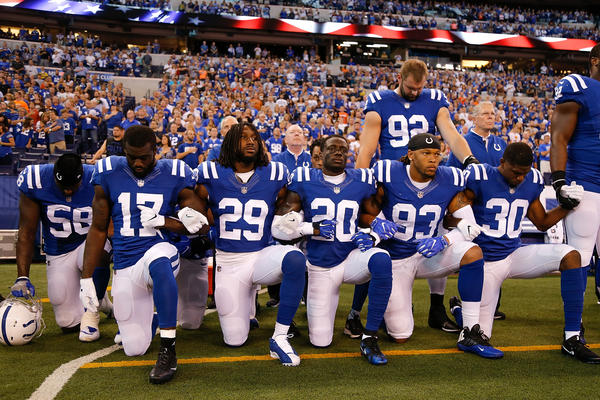 Members of the Indianapolis Colts stand and kneel for the national anthem prior to the start of a Sept. 24 game against the Cleveland Browns at Lucas Oil Stadium in Indianapolis.