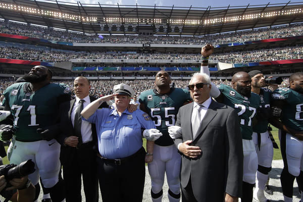 Philadelphia Eagles players and owner Jeffrey Lurie link arms during the national anthem before a Sept. 24 game against the New York Giants in Philadelphia. Malcolm Jenkins, next to Lurie, raises his fist.